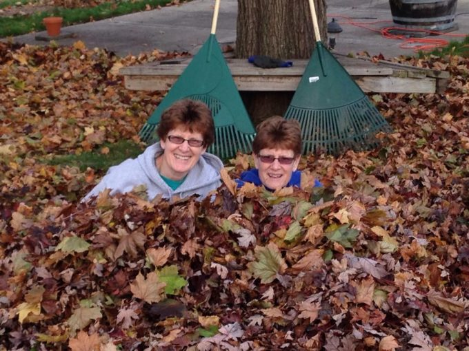 two women in a pile of leaves creators of picnic pasta salad