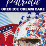 A round ice cream cake with whip cream frosting and patriotic sprinkles on a table with red white and blue star decorations.