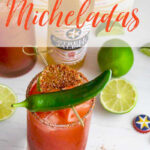 Homemade Micheladas in tall clear glasses and garnished with a chile pepper and a slice of lime with Mexican beer bottles in the background.