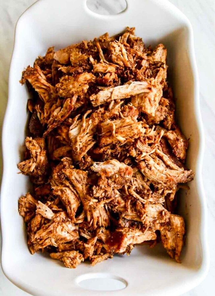 A white casserole dish with roasted pulled pork just out of the oven and seasoned with bbq rub.