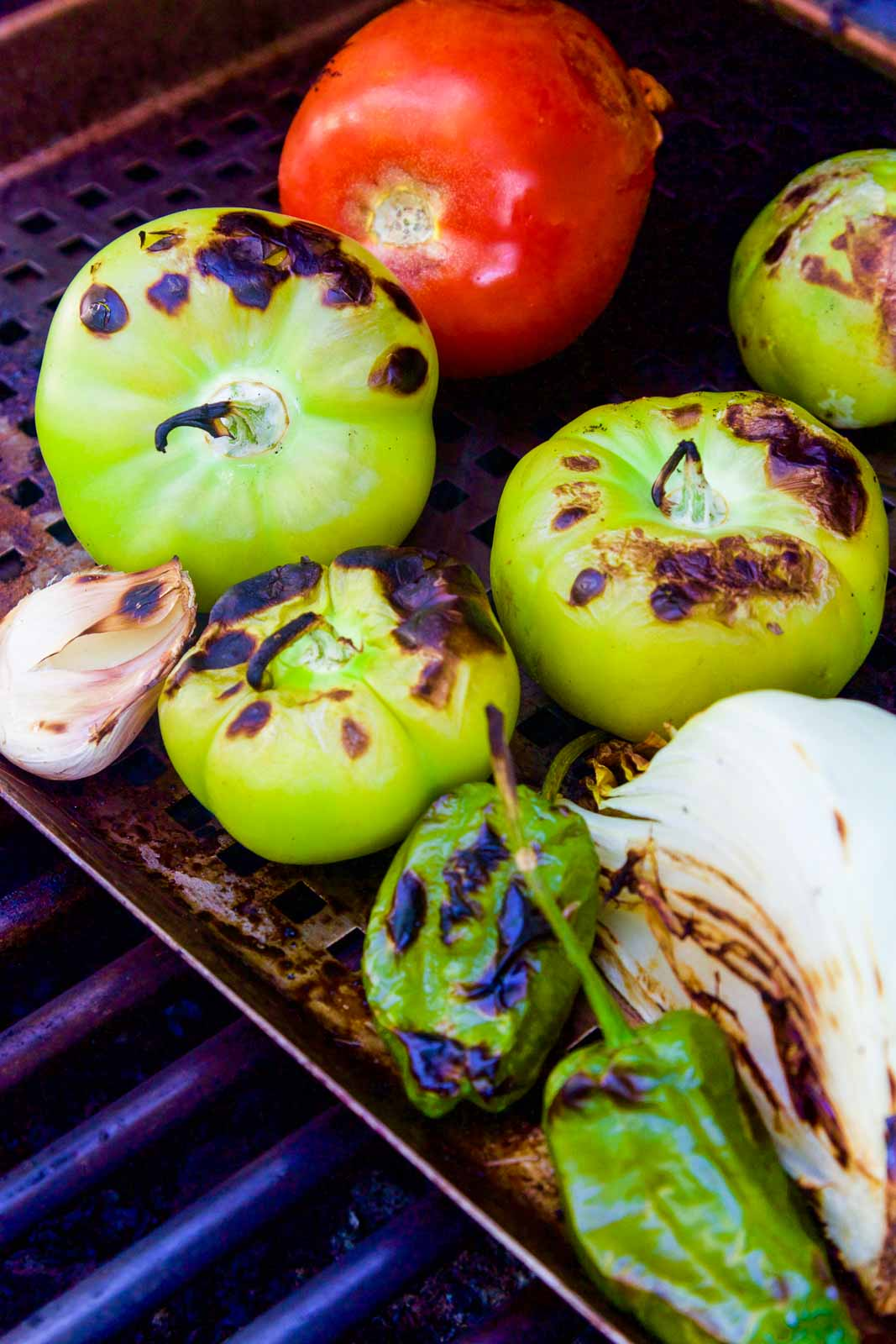 Grilling all the ingredients to make homemade tomatillo salsa on a hot grill including tomatoes, tomatillos, onion, chiles, and garlic.