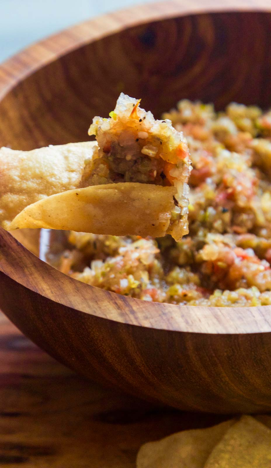 A wooden bowl with a curved tortilla scoop of homemade tomatillo salsa on it ready to take a bite.