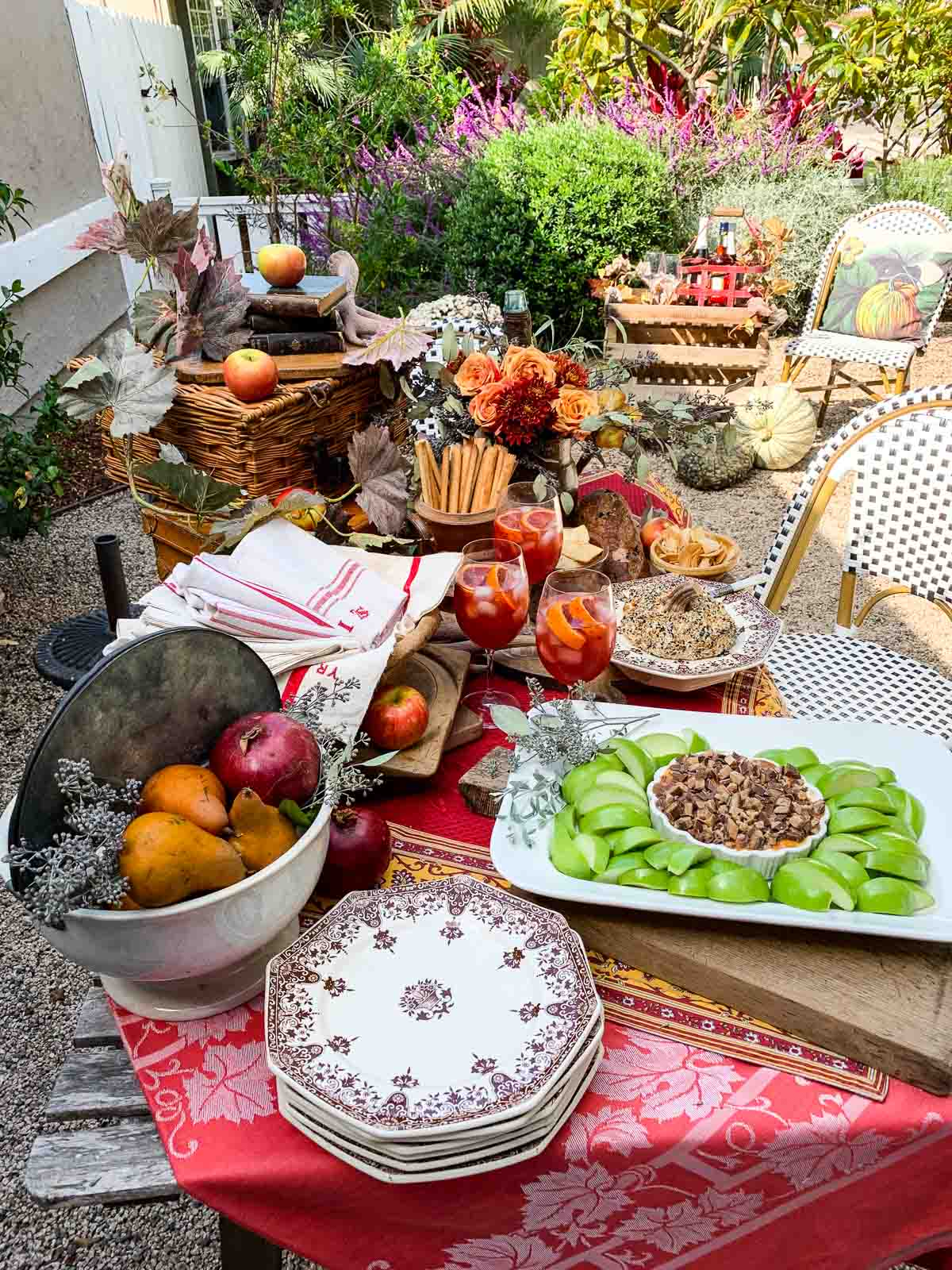 A gorgeous Fall table with French printed red linens and bright colored appetizers featuring and caramel apple dip, pumpkin shaped everything bagel cheese ball, and aperol cocktails at a Fall appetizer outdoor party.