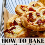 A vintage silver wire basket with freshly baked brie and bacon palmiers made from store-bought puff pastry to serve as an easy appetizer.