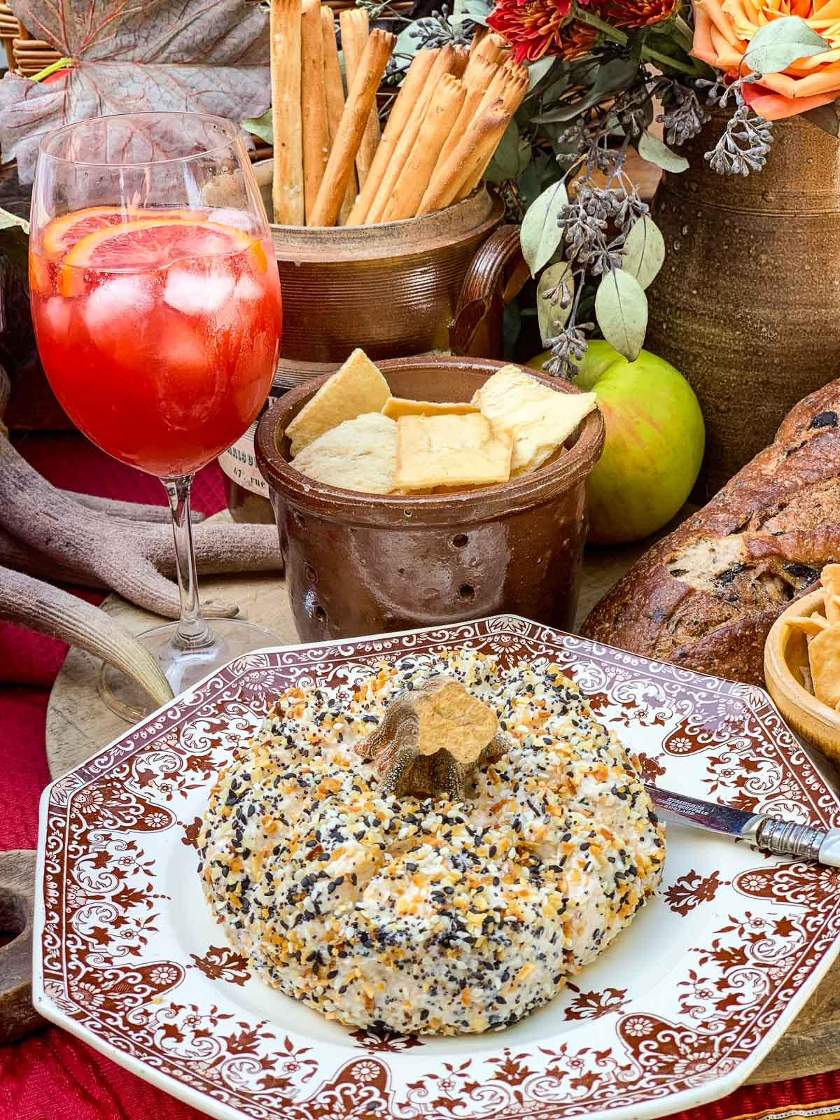 A white and burgandy vintage French plate with pumpkin shaped cheese ball on top, and drinks and snack in the background.
