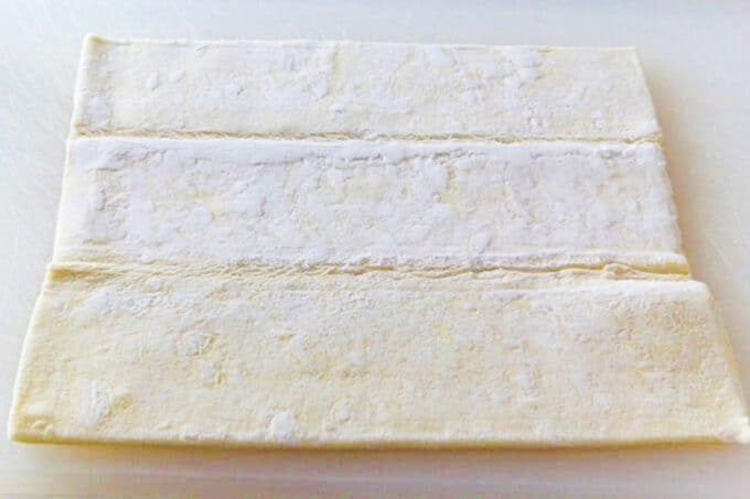 Puff pastry sheets unfolded on a cutting board ready to use in a recipe.