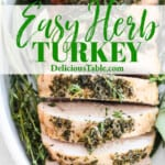 A whole roasted herb turkey breast roast in a white casserole dish surrounded with fresh herbs.