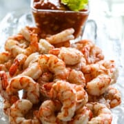 2 lbs of cooked shrimp on a glass platter with cocktail to serve at a party.