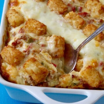 A large white casserole dish with a freshly baked tater tot casserole to serve for a breakfast or brunch party.