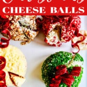 A white square platter with four colorful round cheese balls decorated like Christmas tree ornaments.