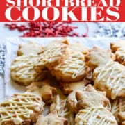 A Pinterest ad for Christmas Shortbread Cookies that are piled on a white plate on a table decorated for Christmas.