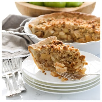 A slice of apple crumble pie on a stack of small white plates with silver forks and a pie in the background.