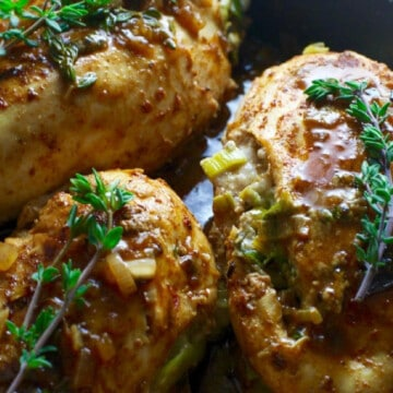 Cooked chicken breasts with a brown sauce in a pan garnished with fresh thyme.
