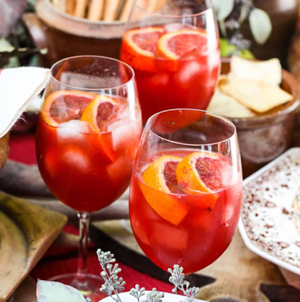 Three glasses of aperol spritz Fall cocktails with appetizers nearby on a table at an outdoor party.