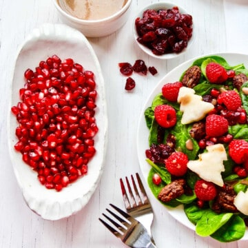 A plate of holiday salad with Christmas tree garnish, raspberries, pecans, cranberries, dressing, and pomegranate seeds.