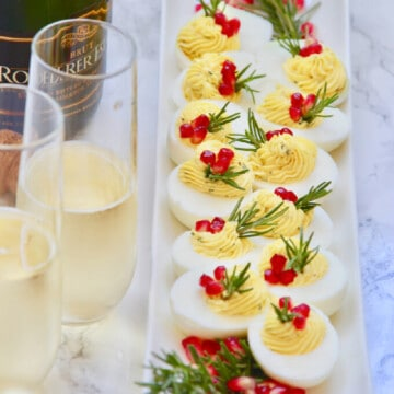 A New Years Eve party with a bottle and glasses of champagne served along side an elegant white platter of holiday deviled eggs.