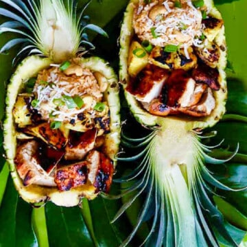 A pineapple sliced in half with grilled chicken, pineapple and rice for a outdoor party.