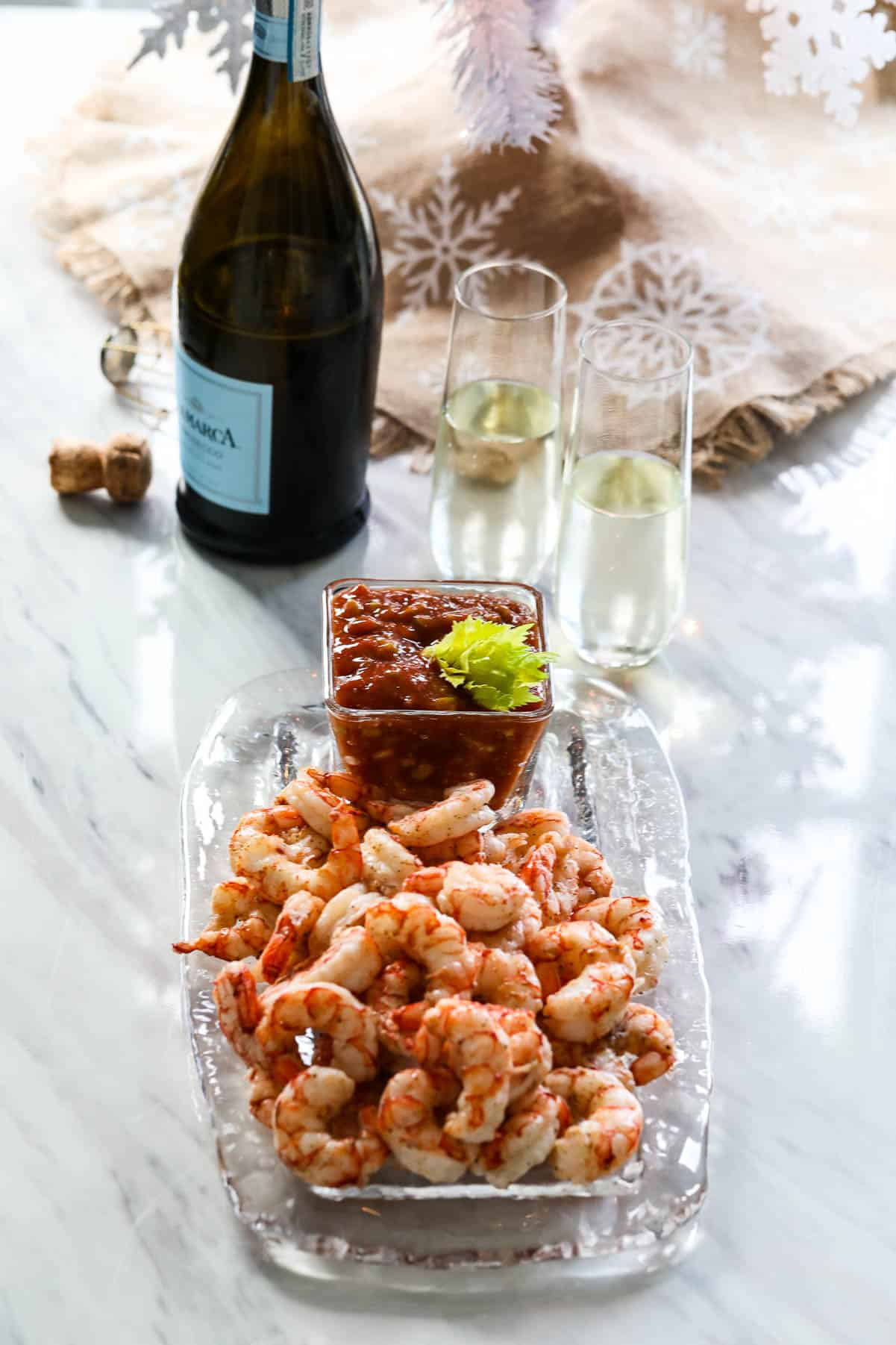Cooked shrimp on a glass platter with cocktail to served at a Christmas party with champagne.