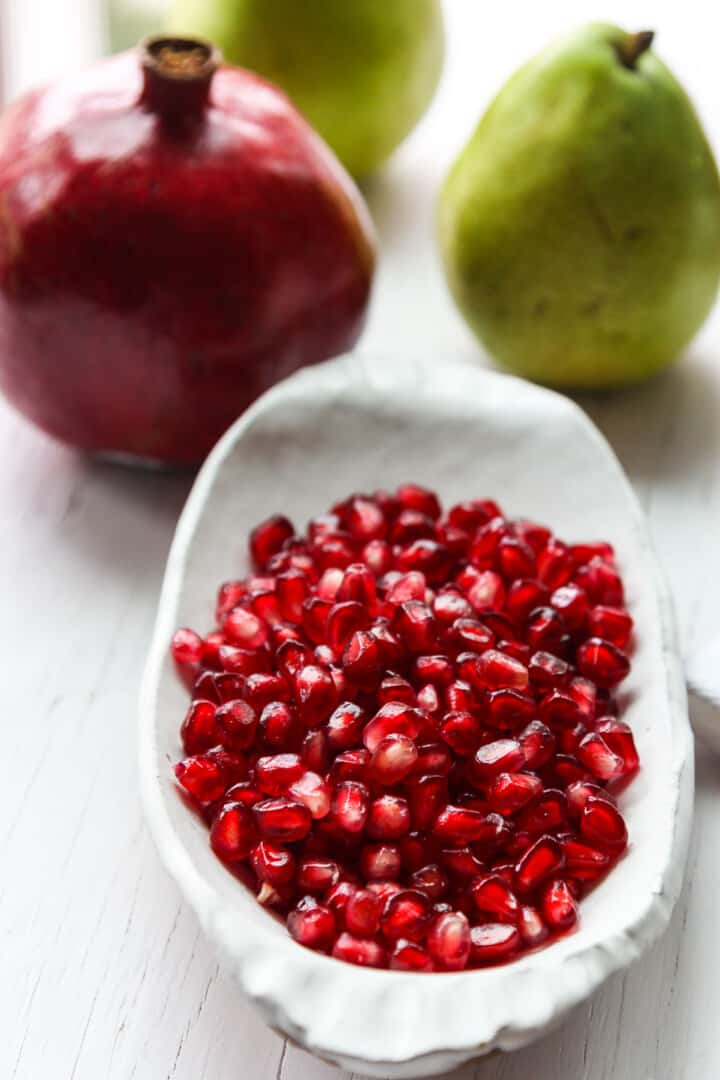 A white ceramic dish filled with red sparkling pomegranate seeds ready to use in a recipe.