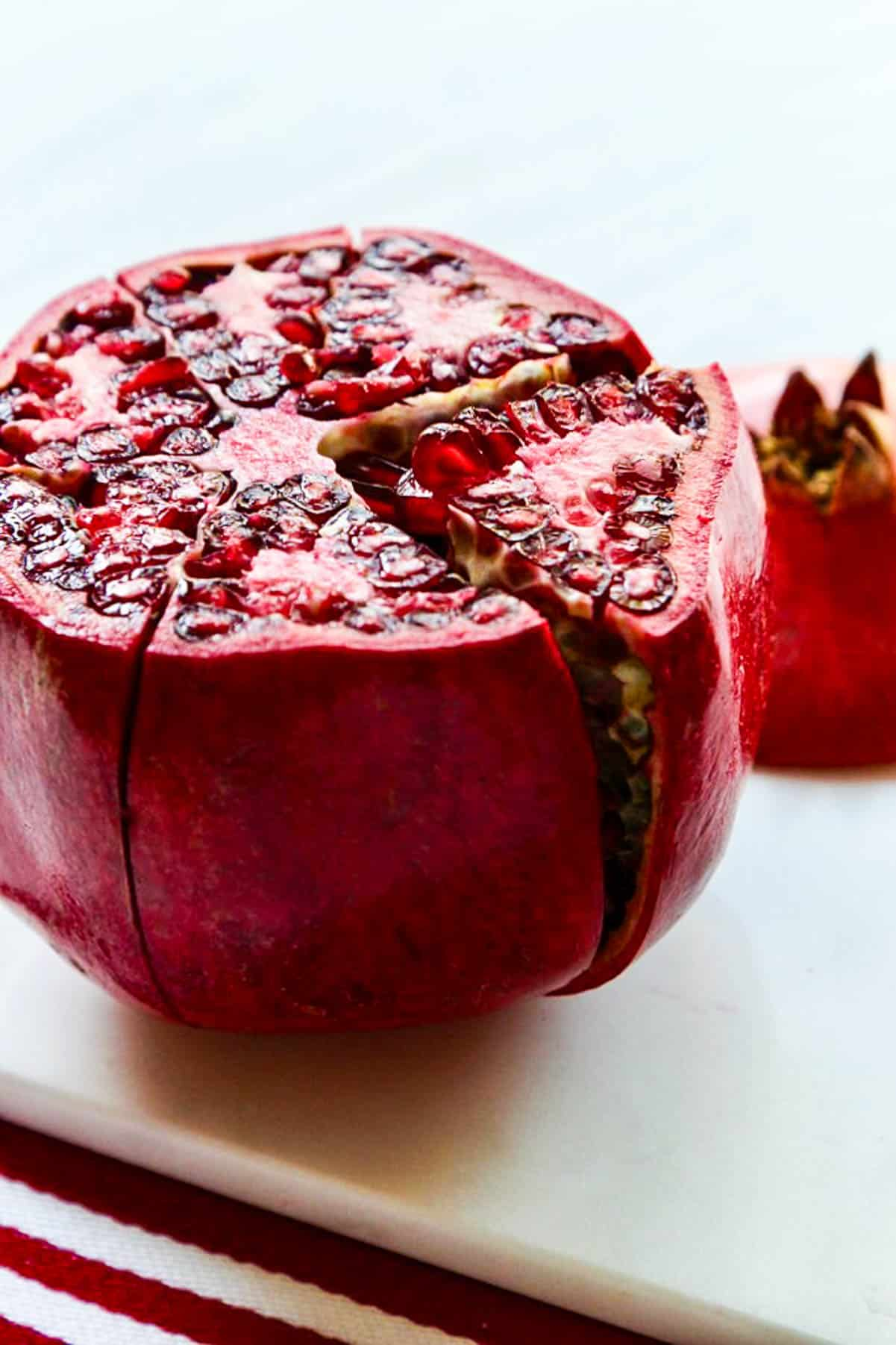A large red pomegranate with the top cut off and cut down the side.
