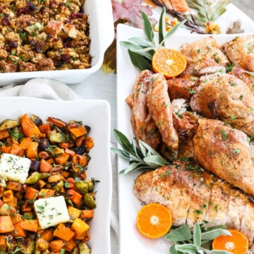 A white holiday table set with a full carved turkey, colorful roasted vegetables, and stuffing ready to eat at a party.