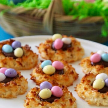 A white cake plate with coconut macaroon cookies decorated with pastel colored chocolate eggs for Easter.