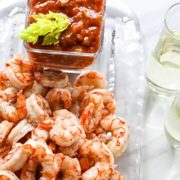 A pile of cooked shrimp cocktail with a small bowl of cocktail sauce.