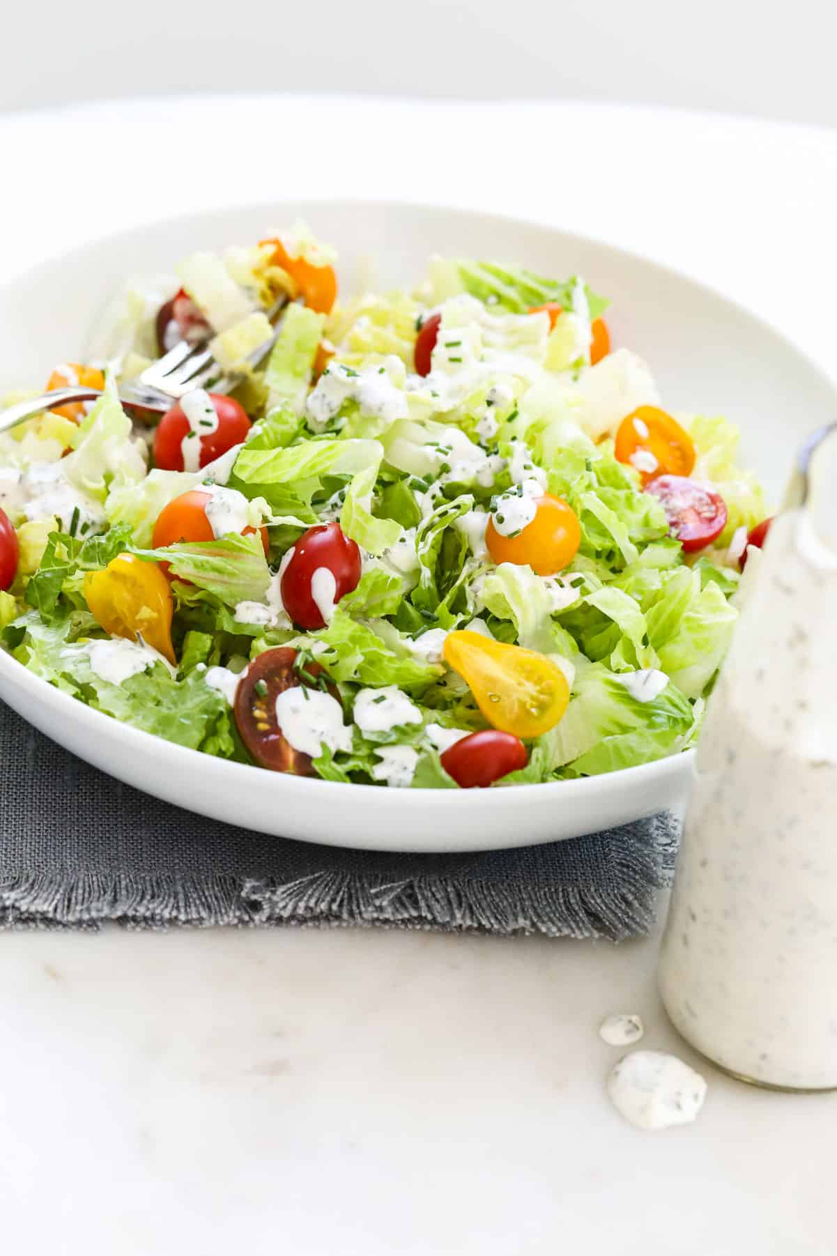 A white round plate filled with colorful green salad topped with ranch dressing.