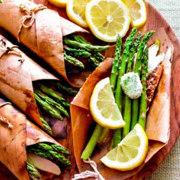 Cedar wrapped grilled salmon with asparagus and lemon slices on a platter.