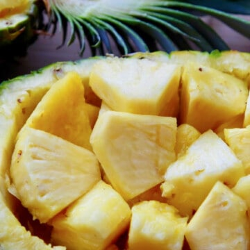 Half a pineapple with stem on a cut pineapple chunks inside the pineapple bowl.