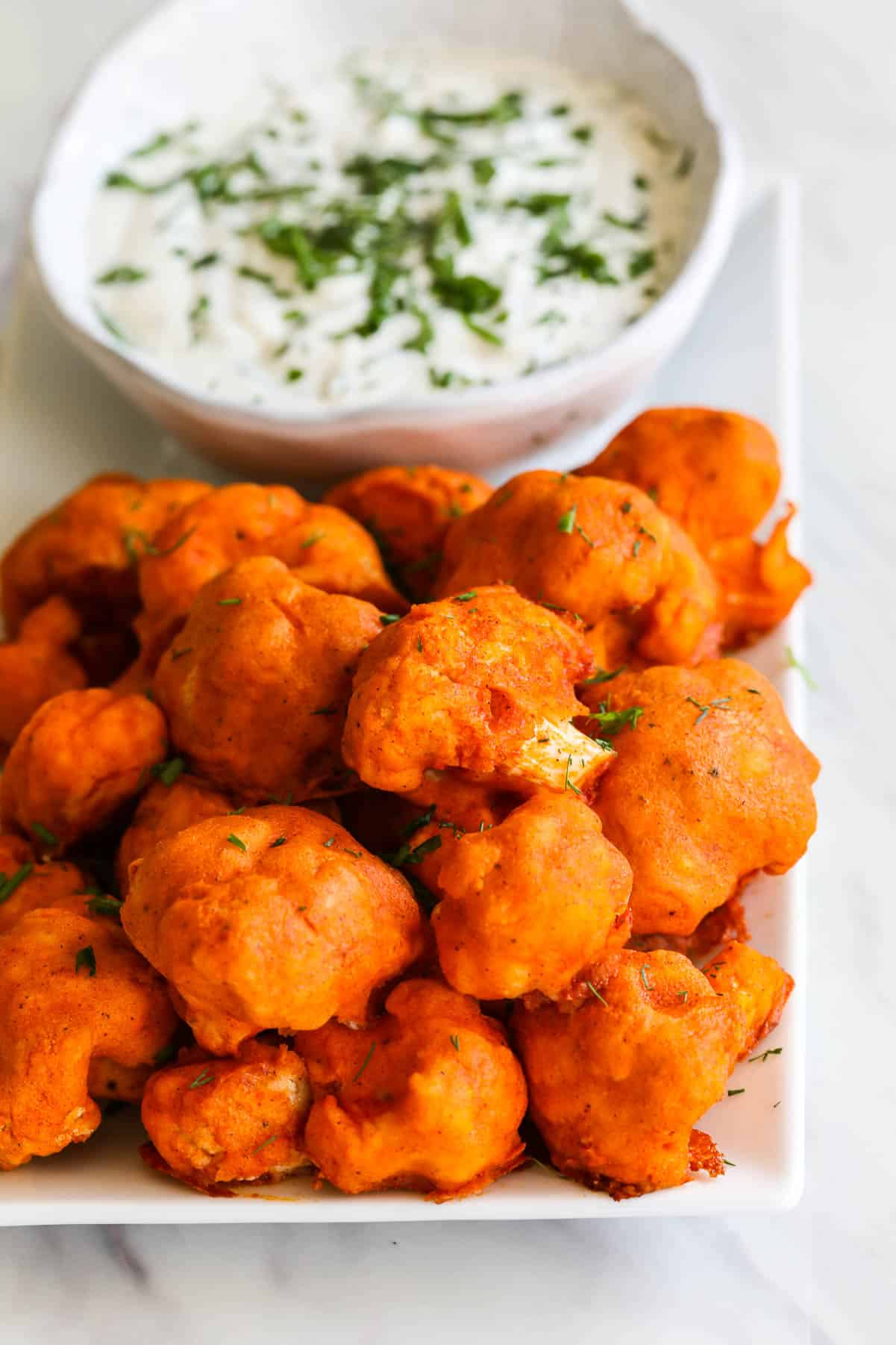 A pile of baked Buffalo Cauliflower on a plate with ranch dip sprinkled with fresh herbs.