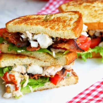 A golden toasted stacked sandwich with chunks of lobster, crisp bacon, lettuce, and tomato.
