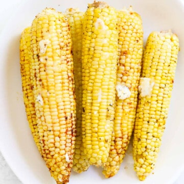 A large white platter with a stack of grilled yellow corn sprinkled with spices and topped with melted pieces of butter.