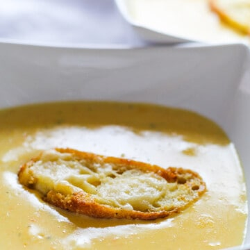 A white bowl filled with cheese soup and a long cheesy crouton floating on top.