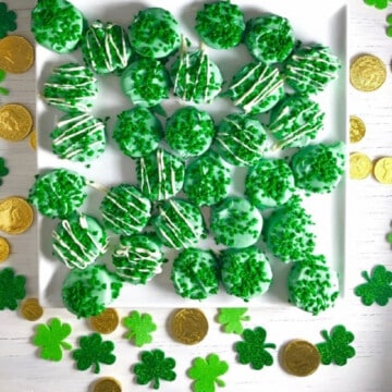 A white board with green iced oreos decorated with shamrocks and gold coins and green shamrocks on the board as decorations.
