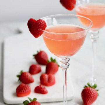 A pink cocktail with a sliced strawberry in the shape of a heart on the edge of the glass as a garnish.
