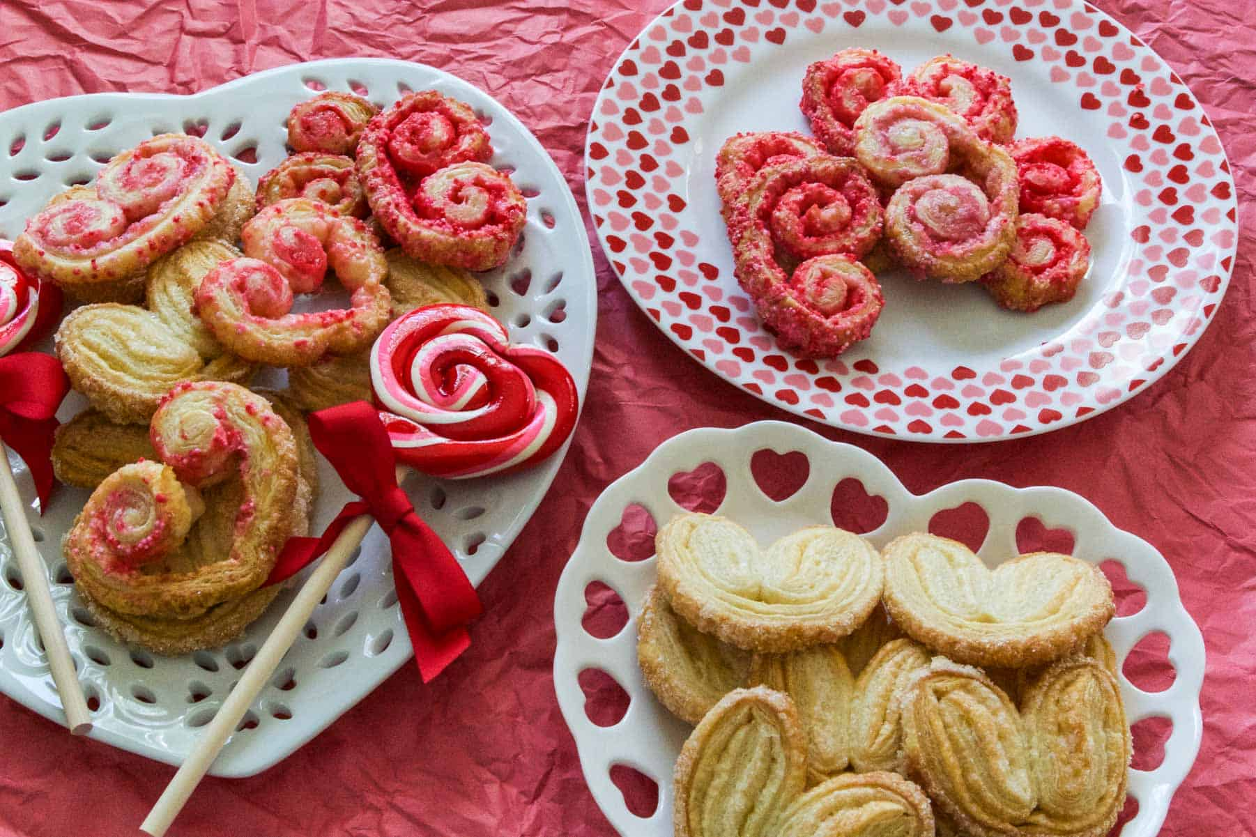 Fresh baked golden brown palmiers on a white shaped heart plate.