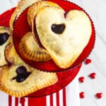 A red cookie plate filled with heart shaped chocolate hand pies.