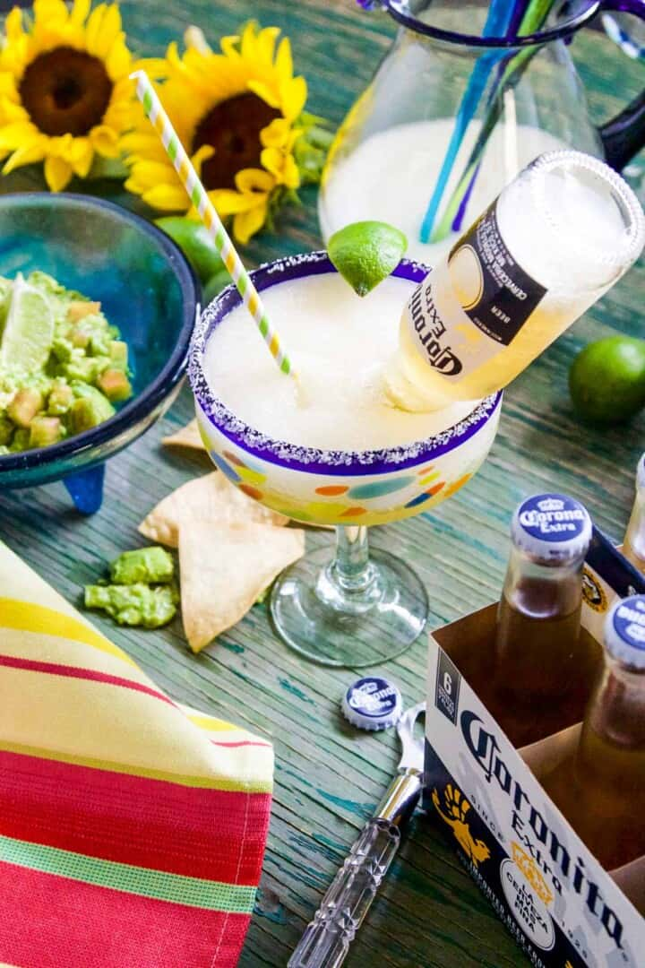 An icy cold slushy margarita with a small Coronita beer inside the glass at a party.
