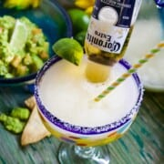A large blue rimmed margarita glass with straw, lime, and Coronita beer poured inside the glass.