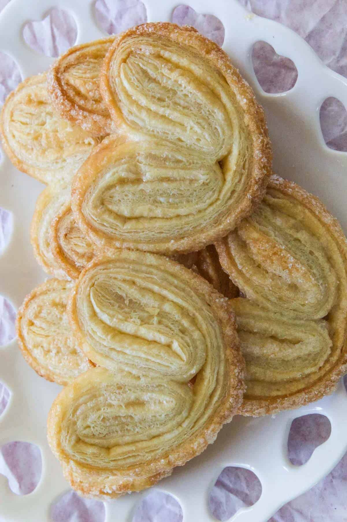 A white heart shaped dish filled with fresh baked palmiers.