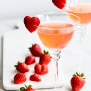 Pink strawberry cocktails with whole berries and heart shaped garnish.