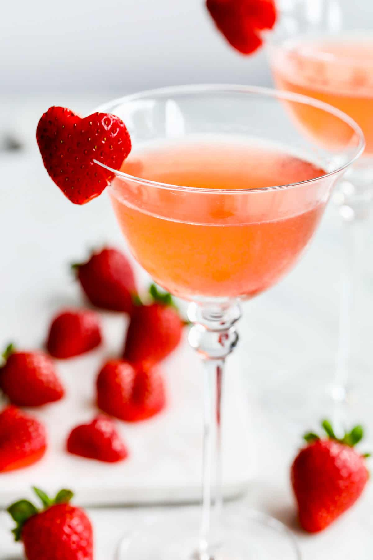 Heart shaped garnish made from strawberry on edge of pink cocktail.