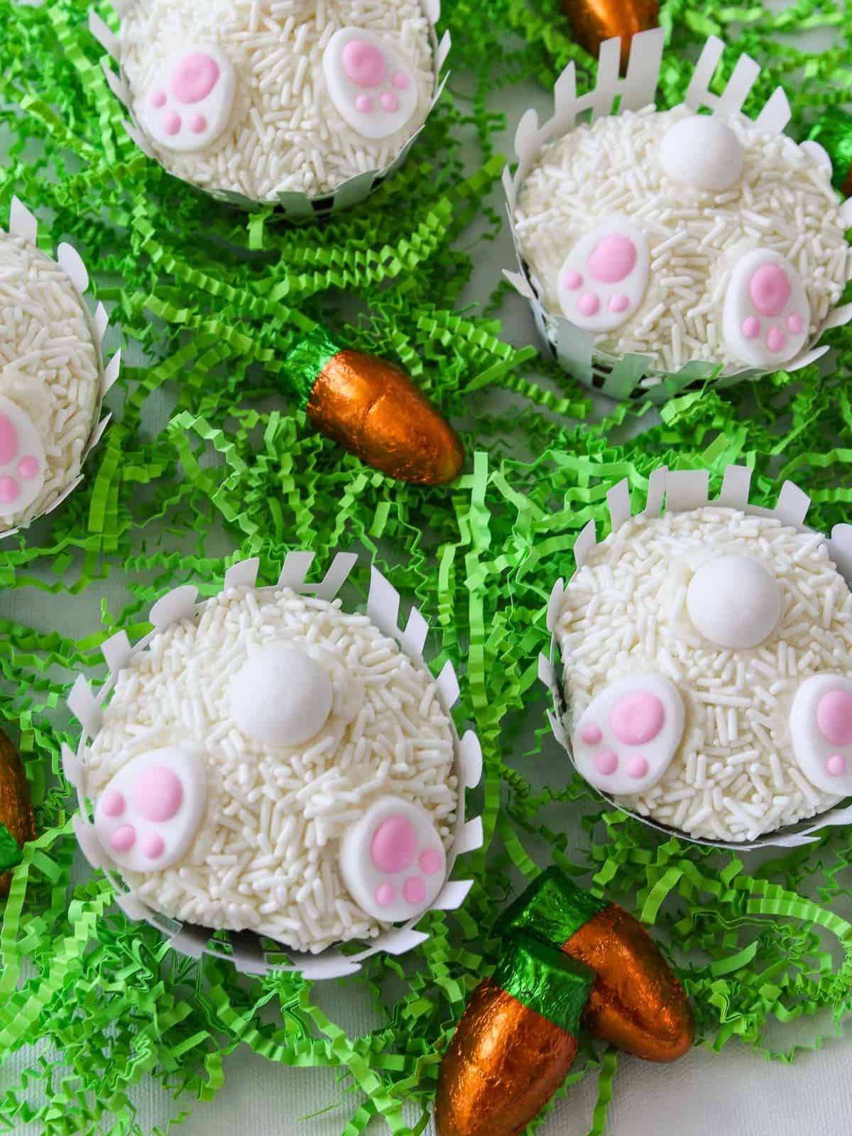 Overhead view of 5 Easter bunny cupcakes on table with green paper grass.