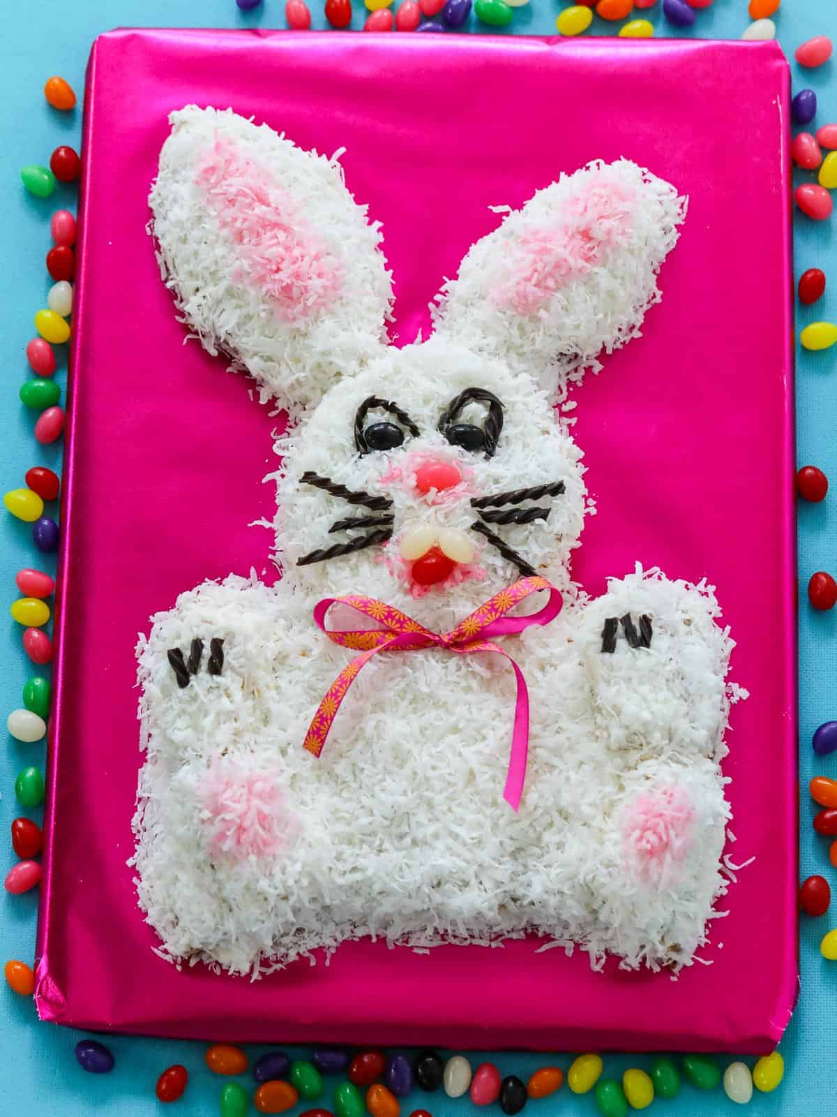 Overhead view of an adorable bunny cake on a hot pink background surrounded with jelly beans.