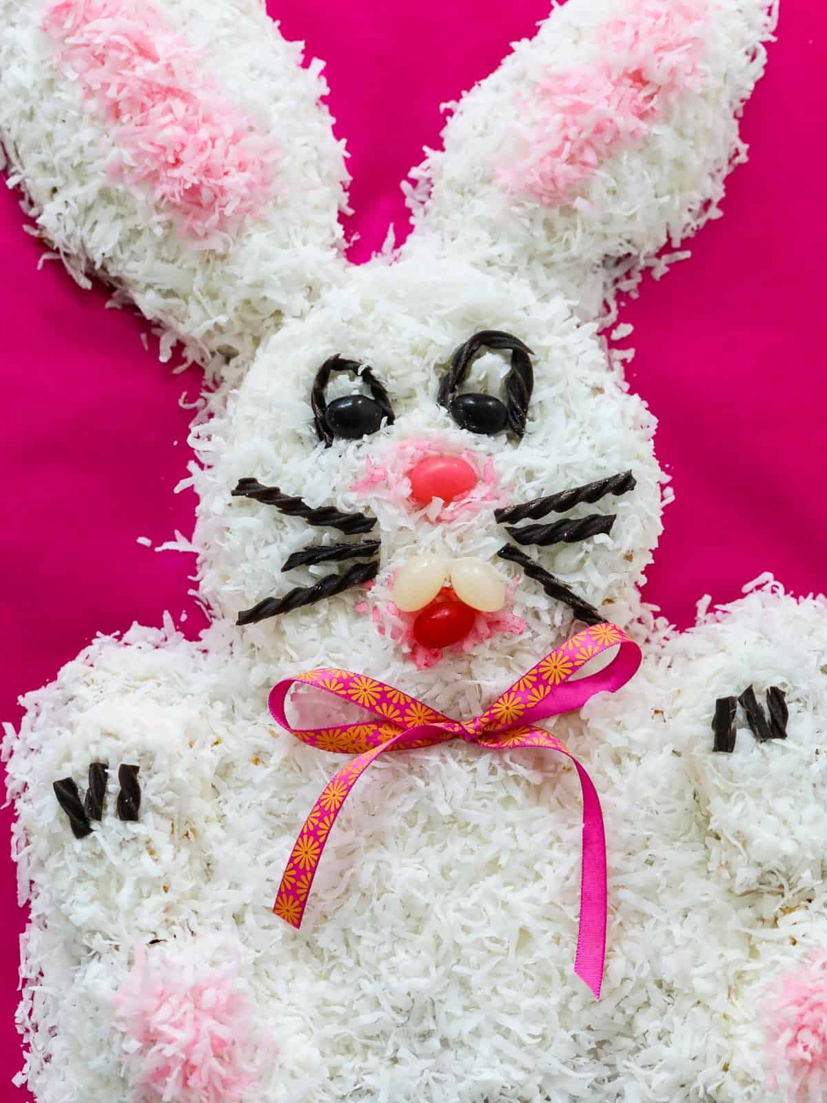 A close up of an Easter cake that is a bunny rabbit, with pink coconut ears and licorice whiskers.