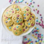 A white plate filled with freshly baked cake mix cookies with pastel m&m candies.