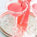 A silver tray with Candy Cane Martinis with crushed peppermint rim and candy cane garnish.