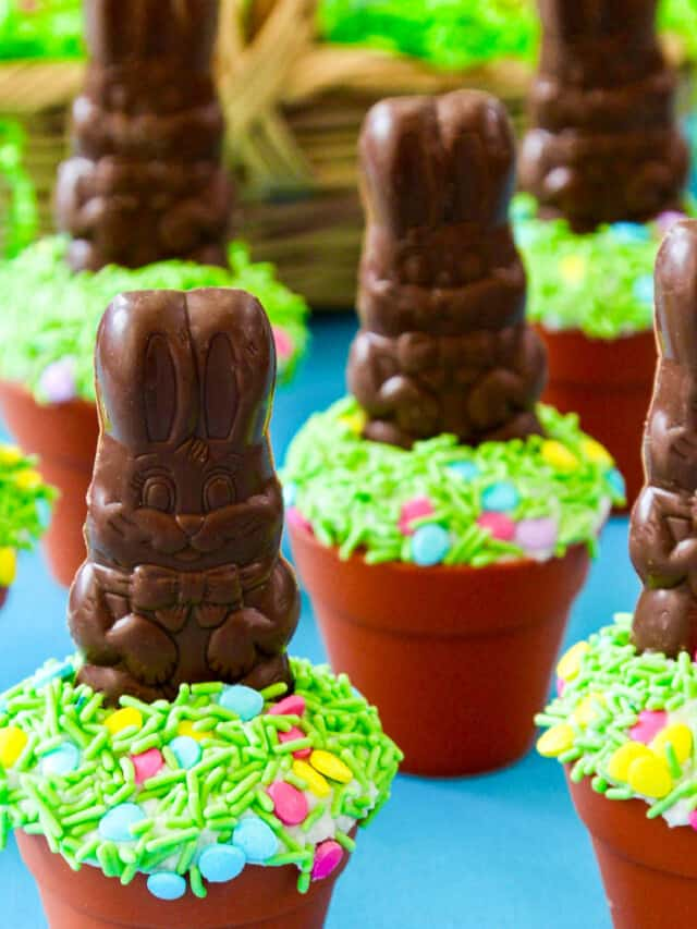 A display of Easter cupcakes decorated with chocolate bunnies and green sprinkles.