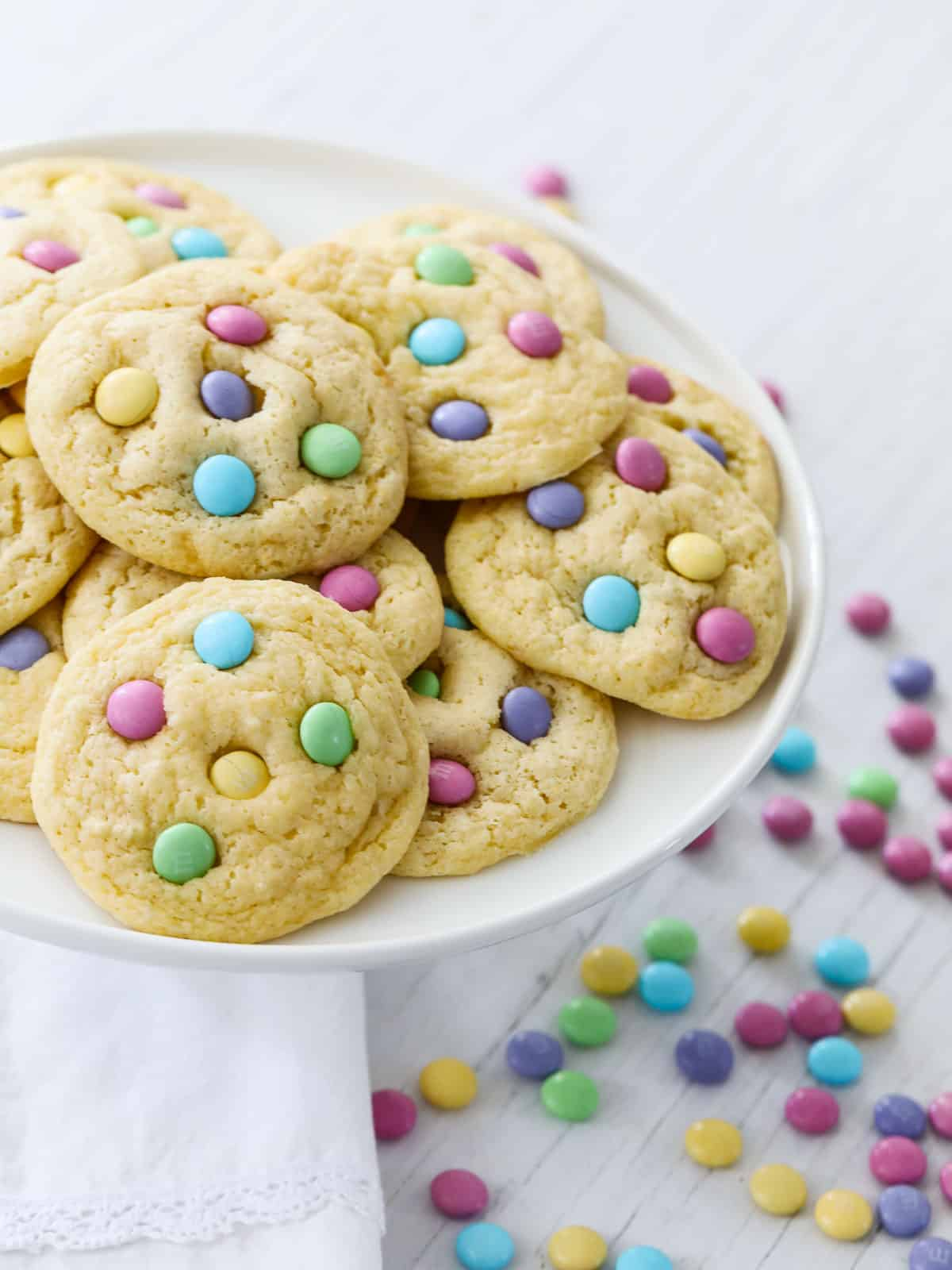 Pastel studded cake mix cookies on white cake plate.